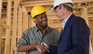 two men in hard hats shaking hands